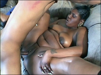 Tattooed ebony fatty is laying on her back with her legs spread wide and is getting fucked hard by her fuckbuddy